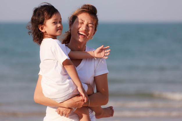 Azjatycka mama i syn bawią się na tropikalnej plaży