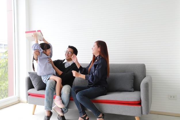 Azjatycka mama i tata siedzą z córką na kanapie z uśmiechniętymi i szczęśliwymi twarzami.