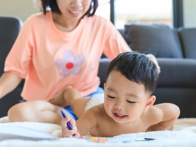 Azjatycka mama uczy jej rysować chłopiec