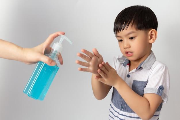 Azjatycka mama używa alkoholowego antyseptycznego żelu do czyszczenia rąk dziecka. dezynfekcja koronawirusem