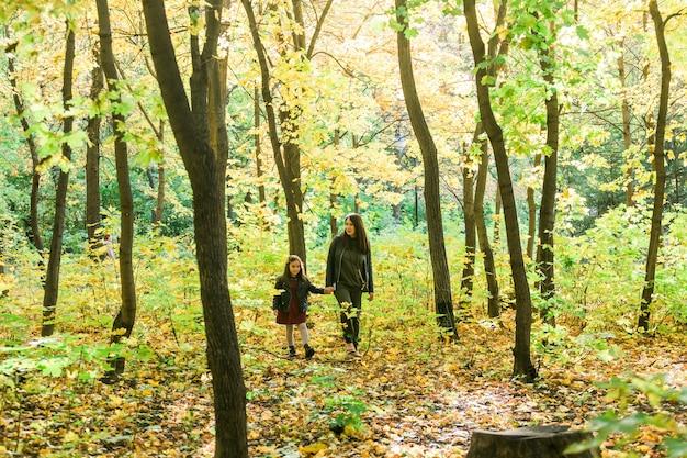 Azjatycka matka i córka chodzą trzymając się za ręce w parku, noszą ciepłe ubrania samotny rodzic