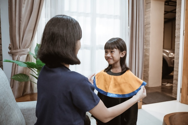 Azjatycka matka i dziecko przygotowują się do jej lepszego dnia absolwentów w domu