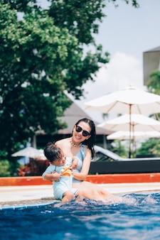 Azjatycka matka i synek, ciesząc się pływaniem w basenie w letnie wakacje.
