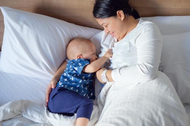 Azjatycka matka karmi piersią śliczny mały azjatycki 14 miesięcy