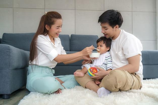 Azjatycka matka karmi swojego 6-miesięcznego chłopca stałym pokarmem z łyżeczką, a ojciec siedzi obok, aby dopingować syna do jedzenia w salonie w domu.