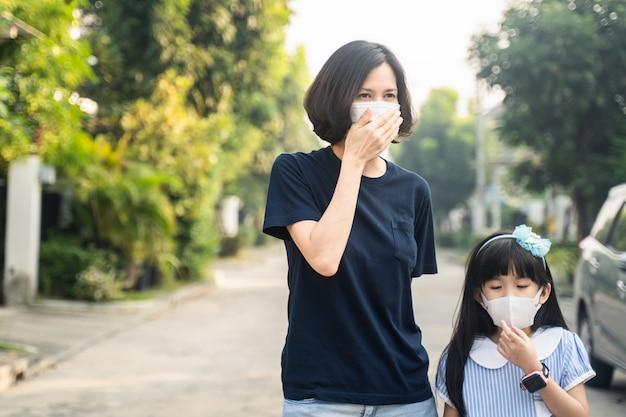 Azjatycka matka, matka i córka małej dziewczynki w masce zapobiegającej covidowi-19