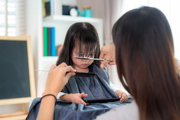 Azjatycka matka obcinająca włosy córce w salonie w domu, podczas gdy w domu jest bezpieczna od koronawirusa covid-19 podczas blokady. samo kwarantanna i dystans społeczny.
