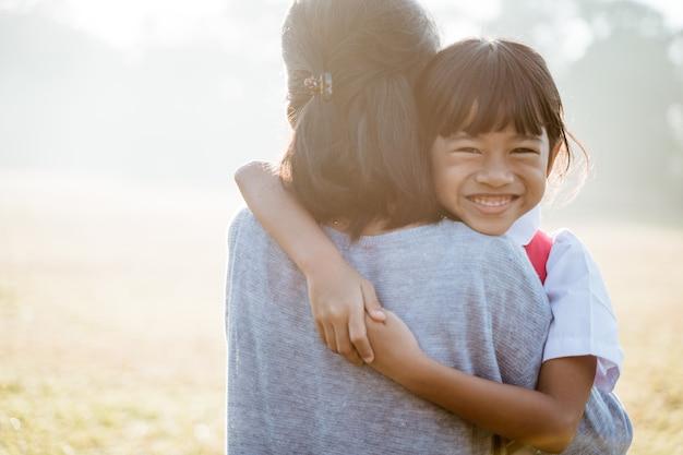 Azjatycka matka obejmuje i przytula córkę idącą do szkoły