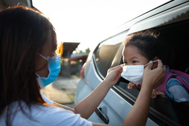 Azjatycka matka pomaga córce w noszeniu maski ochronnej, aby chronić przed epidemią koronawirusa covid-19 przed pójściem do szkoły. przygotuj się do koncepcji szkoły.