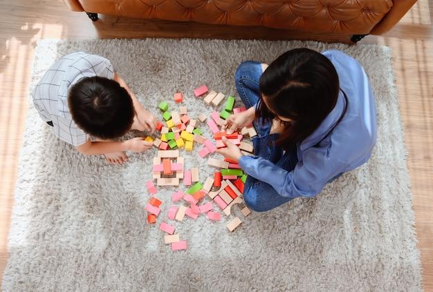 Azjatycka matka pracuje w domu razem z synem. mama i dziecko bawią się kolorowym drewnianym klockiem. dziecko tworząc zabawki budowlane. styl życia kobiety i aktywność rodzinna.