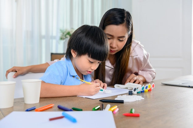 Azjatycka matka pracuje w domu razem z synem. mama i dziecko rysują obraz i kolorową sztukę malowania. styl życia kobiety i aktywność rodzinna.