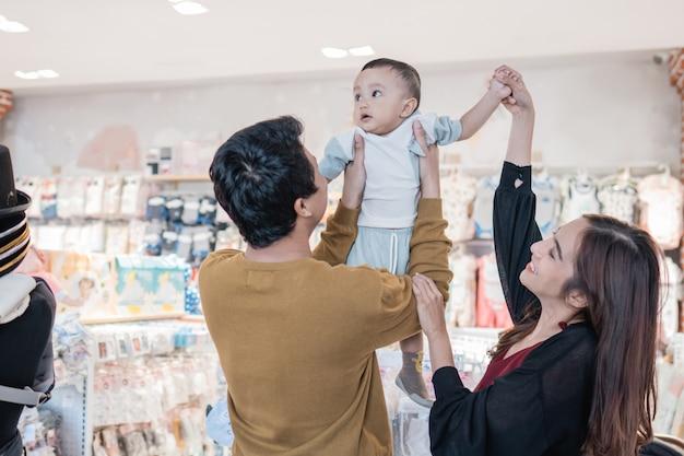 Azjatycka matka z małym chłopcem robi zakupy w sklepie dla dzieci