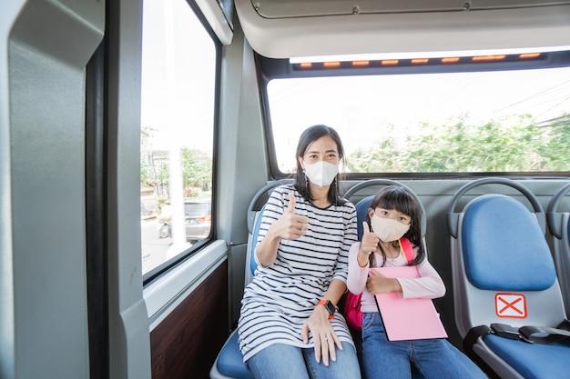 Azjatycka matka zabiera córkę do szkoły jadąc autobusem transportem publicznym w masce na twarz