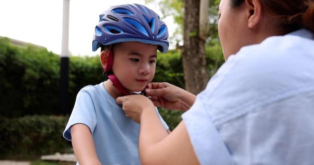 Azjatycka matka zakładająca synowi kask ochronny podczas jazdy na rowerze w publicznym parku