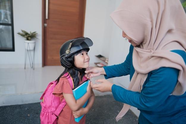 Azjatycka matka zapina hełm swojej córki. zabranie do szkoły motocyklem skuterem rano. uczeń szkoły podstawowej wraca do szkoły