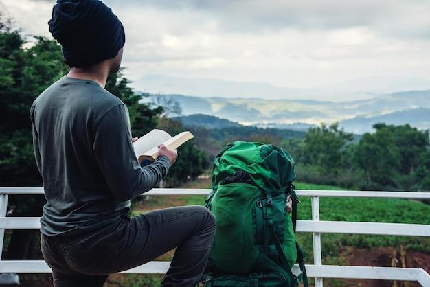 Azjatycka mężczyzna podróż relaksuje w wakacje. siedzenia relaksują się czytając książki w punkcie widokowym na górze. w doi inthanon chiangmai w tajlandii.