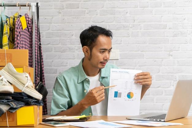 Azjatycka mężczyzna ręka wskazuje przy biznesowym dokumentem podczas dyskusi przy spotkaniem na laptopie