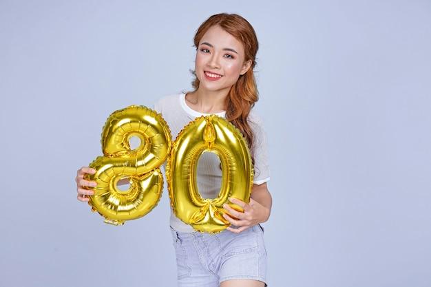 Azjatycka młoda atrakcyjna piękna młoda dziewczyna trzyma numer balonu folii metalicznej
