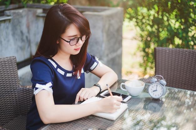 Azjatycka młoda biznesowa kobieta pisze notatce
