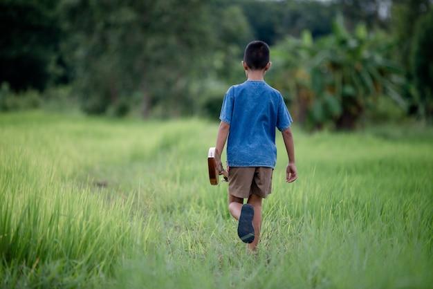 Azjatycka młoda chłopiec z gitarą handmade w plenerowym, życie kraj