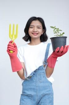 Azjatycka młoda dziewczyna sadzi kwiat nosić jean i białą koszulę z uśmiechniętą twarzą