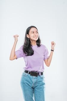 Azjatycka młoda dziewczyna uśmiechnięta szczęśliwa, zaciśnięta w pięści i podniosła dwie ręce na białym tle