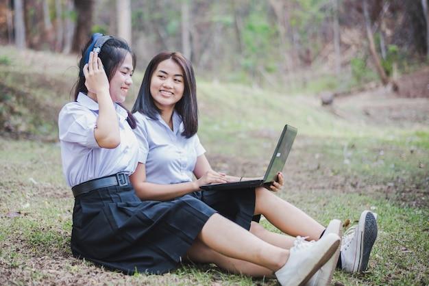 Azjatycka młoda dziewczyna w mundurku szkolnym używa laptop dla edukaci i komunikaci przy wsią tajlandia.