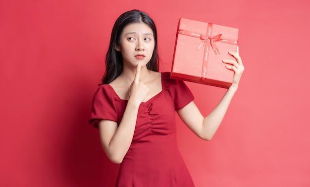 Azjatycka Młoda Dziewczyna W Sukience Trzyma Czerwone Pudełko Z Wesołym Wyrazem Na Tle Premium Zdjęcia