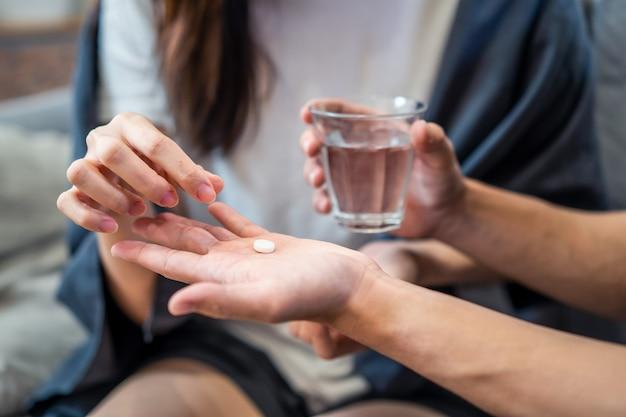 Azjatycka młoda kobieta chora na koronawirusa lub covid-19 siedzi na kanapie, mając lek od chłopaka w domu.