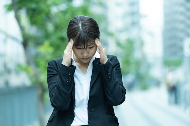 Azjatycka młoda kobieta cierpi na ból głowy