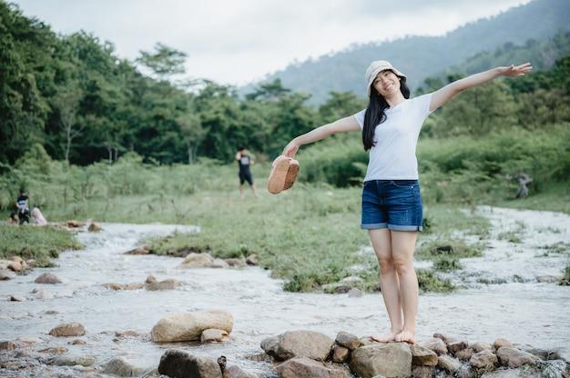 Azjatycka młoda kobieta, ciesząc się i relaksując z naturą, pole strumienia wody, wodospad na zewnątrz