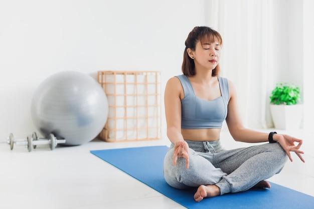 Azjatycka młoda kobieta ćwiczy i gra medytacja jogi w tle w domu. koncepcja ćwiczeń podczas kwarantanny w domu w celu zapobiegania zakażeniu koronawirusem i covid-19.