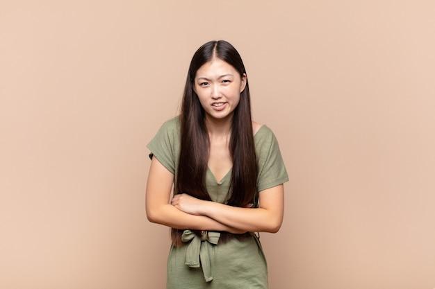 Azjatycka młoda kobieta czuje się niespokojna, chora, chora i nieszczęśliwa, cierpi na bolesny ból brzucha lub grypę