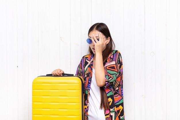Azjatycka młoda kobieta czuje się przestraszona lub zawstydzona, zerkająca lub szpiegująca z oczami do połowy zasłoniętymi rękami.