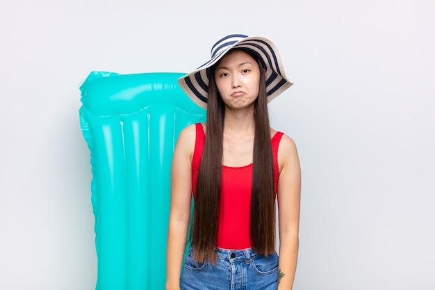 Azjatycka młoda kobieta czuje się smutna i jęczy z nieszczęśliwym spojrzeniem