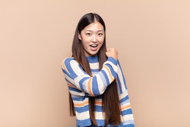Azjatycka młoda kobieta czuje się szczęśliwa, pozytywna i odnosząca sukcesy, zmotywowana, gdy staje przed wyzwaniem lub świętuje dobre wyniki