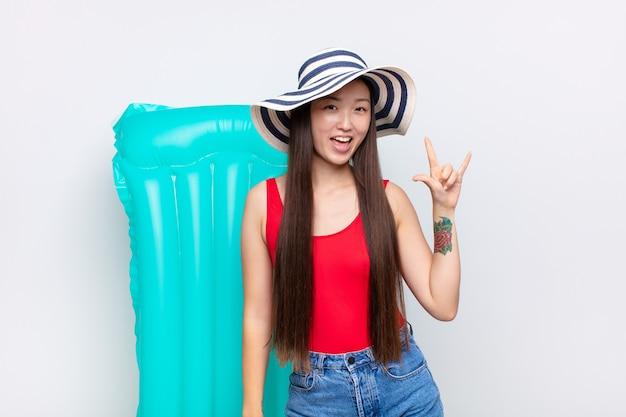 Azjatycka młoda kobieta czuje się szczęśliwa, zabawna, pewna siebie, pozytywna i zbuntowana odizolowana