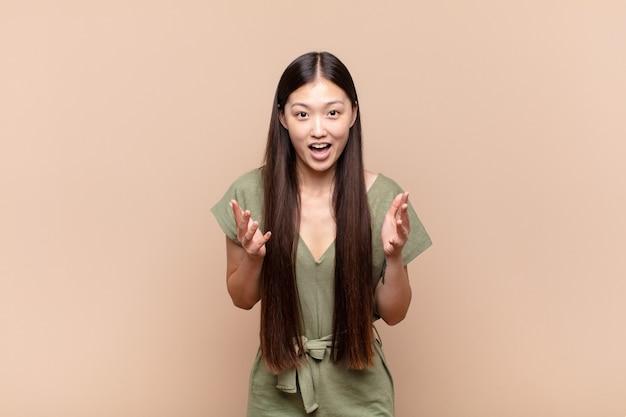 """Azjatycka młoda kobieta czuje się szczęśliwa, zdziwiona, szczęśliwa i zdziwiona, mówiąc poważnie """"omg""""?"""