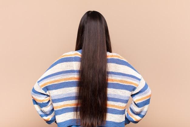 Azjatycka młoda kobieta czuje się zagubiona lub pełna lub ma wątpliwości i pytania, zastanawiając się, z rękami na biodrach, widok z tyłu