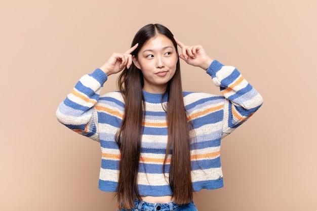 Azjatycka młoda kobieta czuje się zagubiona lub wątpi, koncentruje się na pomyśle, intensywnie myśli, chce skopiować miejsce z boku