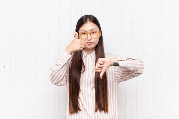 Azjatycka młoda kobieta czuje się zagubiona, nieświadoma i niepewna, ważąc dobro i zło w różnych opcjach lub wyborach