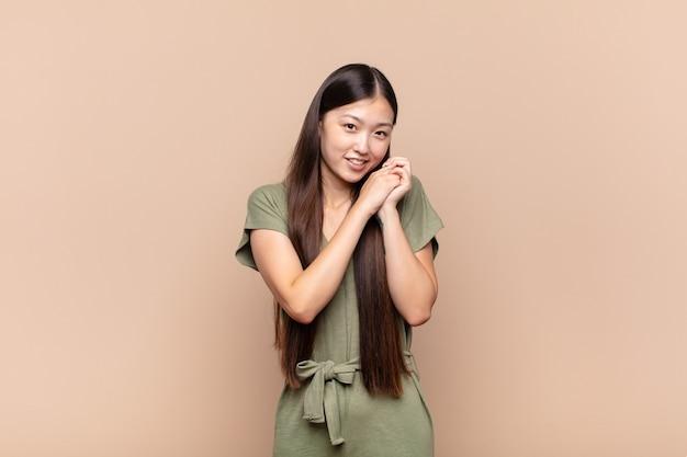 Azjatycka młoda kobieta czuje się zakochana i wygląda słodko, uroczo i szczęśliwie, uśmiechając się romantycznie z rękami przy twarzy