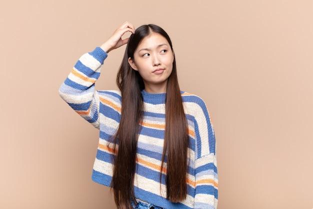 Azjatycka młoda kobieta czuje się zdziwiona i zdezorientowana, drapiąc się po głowie i patrząc w bok
