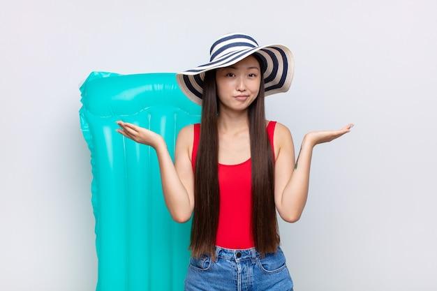 Azjatycka młoda kobieta czuje się zdziwiona i zdezorientowana, wątpi, waży lub wybiera różne opcje z zabawnym wyrazem twarzy. koncepcja lato