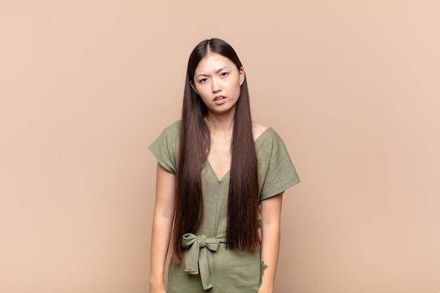 Azjatycka młoda kobieta czuje się zdziwiona i zdezorientowana, z głupim, oszołomionym wyrazem twarzy, patrząc na coś nieoczekiwanego