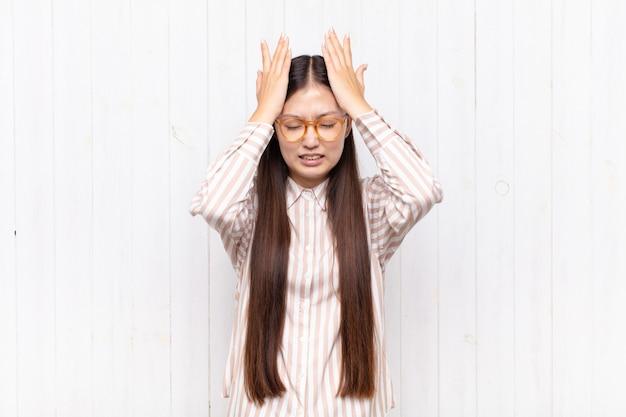 Azjatycka młoda kobieta czuje się zestresowana i niespokojna, przygnębiona i sfrustrowana bólem głowy, podnosząc obie ręce do głowy