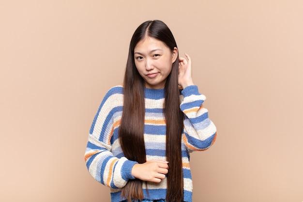 Azjatycka młoda kobieta czuje się zestresowana, sfrustrowana i zmęczona, pocierając bolesną szyję