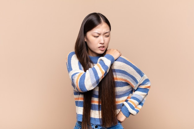 Azjatycka młoda kobieta czuje się zmęczona, zestresowana, niespokojna, sfrustrowana i przygnębiona, cierpi na ból pleców lub szyi