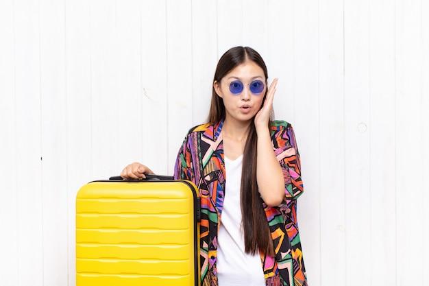 Azjatycka młoda kobieta czuje się zszokowana i zdumiona, trzymając się z niedowierzaniem twarzą w twarz z szeroko otwartymi ustami. koncepcja wakacji