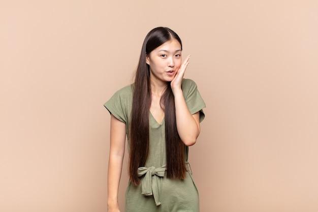Azjatycka młoda kobieta czuje się zszokowana i zdziwiona trzymając twarz
